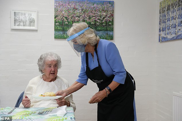 Duchess of Cornwall dons Burberry coat as she serves lunch to to volunteers in a plastic visor 4