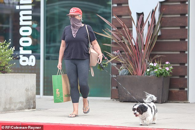 Ricki Lake sports a black T-shirt and leggings for a pet store run with her beloved dog Mama 16